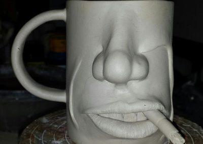 Krus med ansigt og cigaret i munden