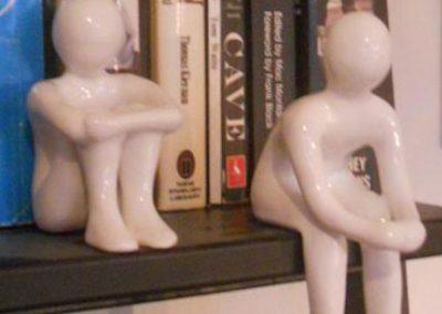 Små mænd lavet af ler der sidder på boghylde