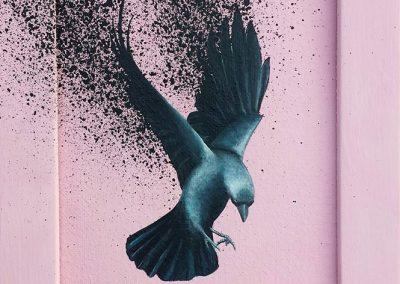 Maleri af fugl der splatter sort på lyserød baggrund