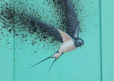 Maleri af fugl der splatter sort på grøn baggrund