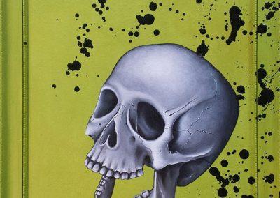 Maleri af et glad kranie og sorte pletter på gul baggrund